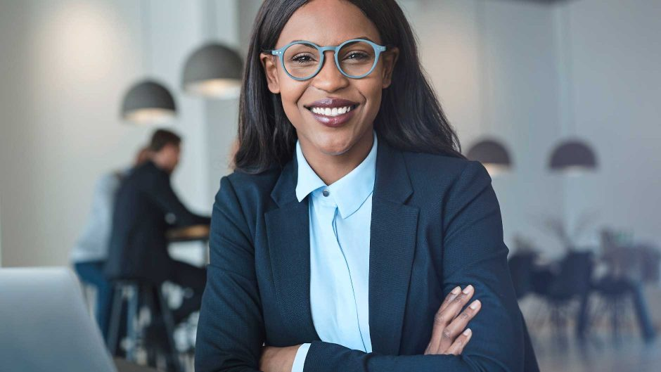 An African American woman in a blue blazer with trendy eyeglasses smiles at the camera